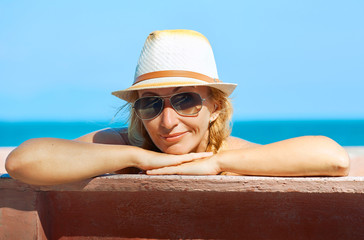 a smiling woman looking at the camera on the sea background