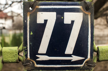 Weathered enameled plate number 77