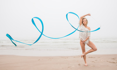 gymnast woman dance with ribbon on the beach
