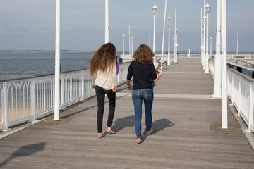 Rear view  of two girls  who strolls on beach