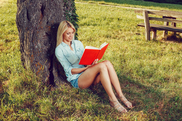 Beautiful young woman reading a book leaning on a tree