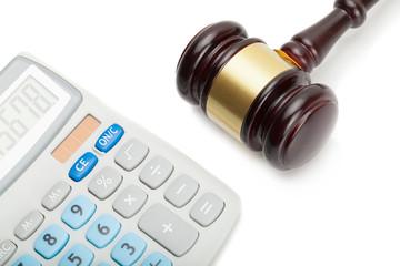 Wooden judge's gavel next to neat calculator