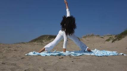 Trikonasana,tringle yoga pose at the sea-side