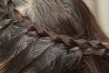 Hairdresser make braids on long hair