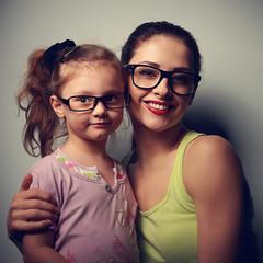 Smiling woman and happy kid girl in eyeglasses looking happy