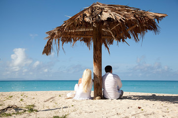 couple sitting under palm umbrella