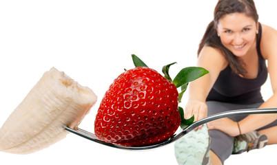 sportliche Frau und Gabel mit Erdbeere und Banane