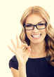 Young businesswoman in glasses with okay gesture