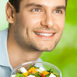 Young happy man with salad, outdoors