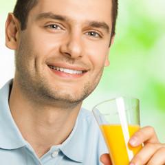 Portrait of smiling man drinking orange juice, outdoors