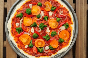 Raw round pizza with yellow cherry tomatoes, onion, garlic and b