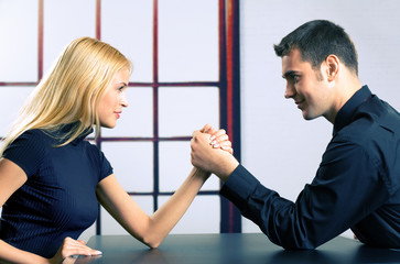 Couple or two businesspeople fighting in arm wrestling