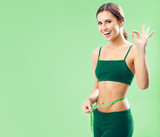 Woman in fitness wear with tape, on green