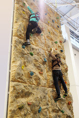 Two boys climbing up on practice wall in gym, rear view