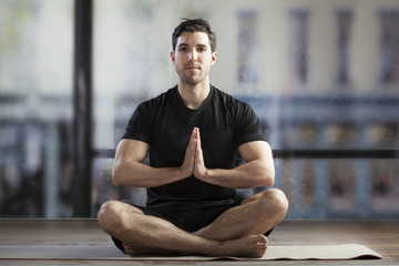 young man doing yoga in office