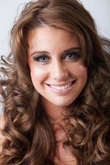 Cute smiling young woman with healthy long curly hair
