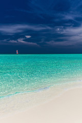 Paradise beach in Maldives with single red sail boat