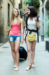 Two european girls on road to hotel on foot