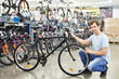 Man checks bicycle before buying in sport shop