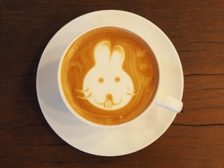 "Latte Coffee art ""Rabbit Face"" on the wooden desk."
