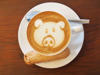 "A Latte Coffee art ""Pig Face"" on the wooden desk."