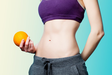 Woman showing her abs with orange after weight loss