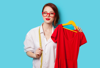Young redhead designer with red dress