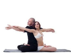 Muscular man and skinny girl practicing yoga