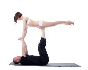 Couple of yoga trainers practising in studio