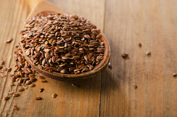 Flax seeds heap on a old  wooden spoon.