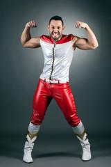 Cheerful muscular dancer shows biceps at camera