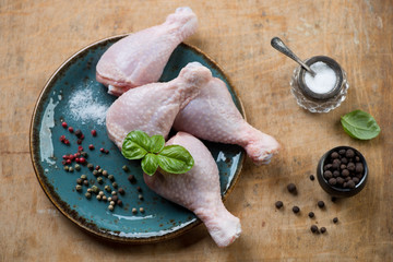 Raw chicken legs with spices and basil, above view, studio shot