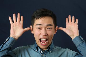Funny young Asian man making face and looking at camera