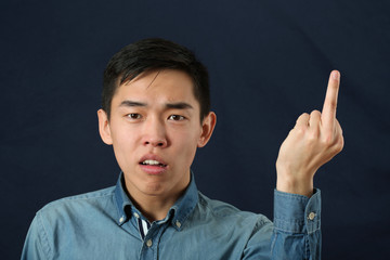 Angry young Asian man giving the middle finger sign and looking