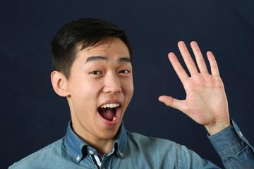 Smiling young Asian man waving his palm and looking at camera