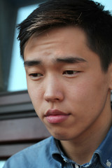 Handsome young Asian man looking downward