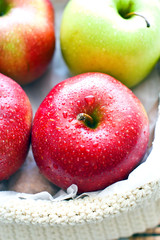 желтое яблоко среди красных яблок
