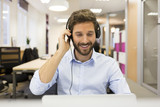 Fototapety Smiling Businessman in the office on video conference, headset,