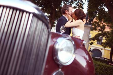 Bride and groom having fun near retro car