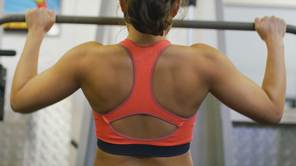 Woman's back as she works out on weights machine