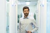 Portrait of handsome bearded business man in corridor office