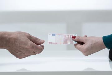 Female hand giving ten euro