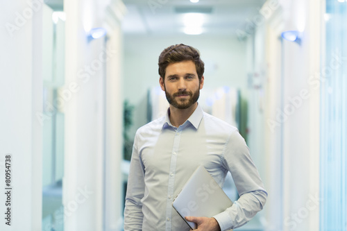 Portrait of handsome bearded business man in corridor office - 80954738