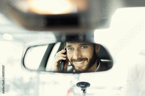 Leinwanddruck Bild Cheerful man on mobile phone in the car