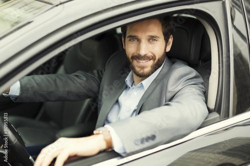 Fototapeta Portrait of man in his car. looking at camera