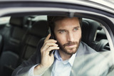 Fototapety Casual business man on mobile phone in rear of the car