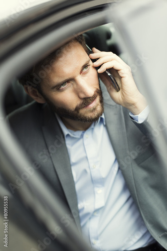 Casual business man on mobile phone in rear of the car