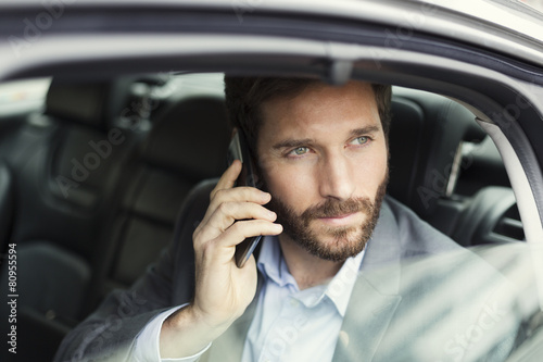 Leinwanddruck Bild Casual business man on mobile phone in rear of the car