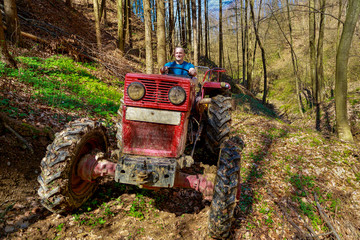 farmer driving a old tractor in forest
