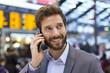 Leinwanddruck Bild - Cheerful man on the mobile phone in hall station